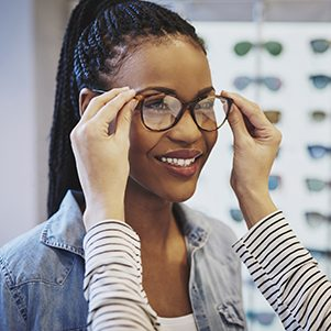 Attractive young African woman selecting glasses with the help of an optometrist in a store trying on different frames